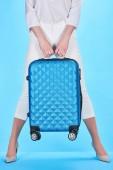 částečný pohled na ženu představující modrý barevný cestovní pytel na modrém pozadí
