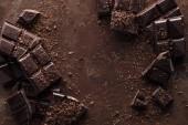 Pohled na kousky čokoládového baru s čokoládovými hranolky na rezavě kovové pozadí