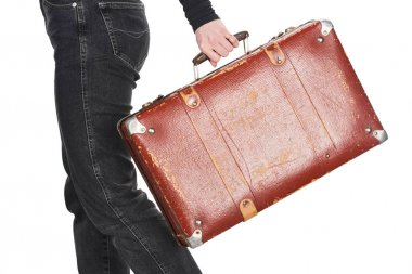 Cropped view of woman in jeans holding vintage weathered suitcase isolated on white stock vector
