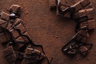 Top view of pieces of chocolate with liquid chocolate and cocoa powder on metal background