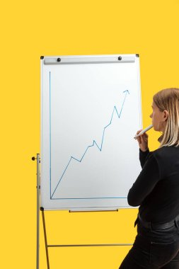 Back view of businesswoman standing near white flipchart, looking at growth graphic, standing isolated on yellow stock vector