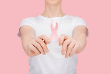 Partial view of woman in white t-shirt holding pink breast cancer sign isolated on pink stock vector