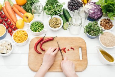 Cropped view of woman cutting chili peppers on wooden chopping board on  white table stock vector