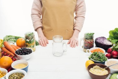 Cropped view of woman in apron with empty jar and vegetables on wooden table isolated on white stock vector