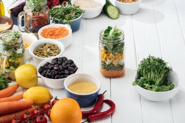 greens in bowl near fruits and vegetables in glass jar on wooden white table