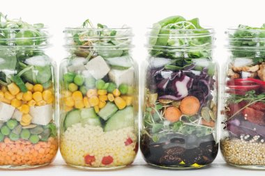 fresh vegetable salad in glass jars isolated on white