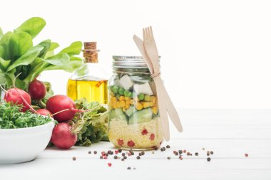 Fresh vegetable salad in glass jar near oil, radish and spices isolated on white stock vector