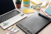 Zeichnungstablette, Schreibwaren und Laptop auf Holztisch
