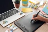 oříznutý pohled na ženu pracující s kreslicím tabletem, sedící za dřevěnou tabulkou s papírnickým stolem a laptopem