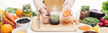 Cropped view of woman in apron adding carrot slices to glass jar with beans on wooden table isolated on white, panoramic shot stock vector