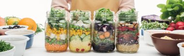 cropped view of woman in apron with glass jars with salad on wooden table isolated on white, panoramic shot