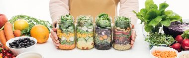 cropped view of woman with glass jars with salad on wooden table isolated on white, panoramic shot
