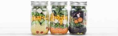 delicious vegetable salad in jars on wooden white table isolated on white, panoramic shot