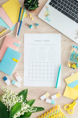 top view of monthly planner, stationery, flowers and laptop on wooden table