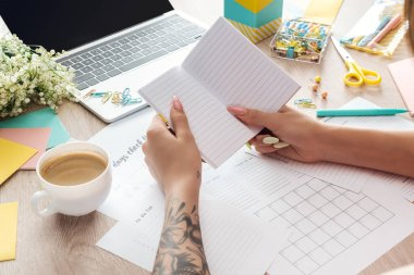 cropped view of woman holding notepad in hands, working behind wooden table with cup of coffee, stationery, laptop and flowers