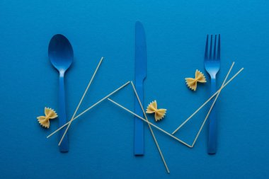Blue plastic cutlery with spaghetti and farfalle pasta on blue background stock vector