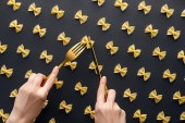 cropped view of woman holding yellow fork and cutting farfalle pasta with knife isolated on black