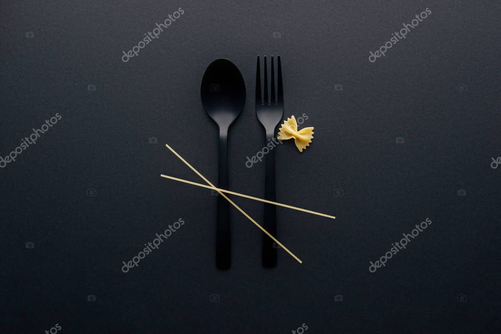top view of spaghetti noodles on plastic cutlery near farfalle pasta on black background