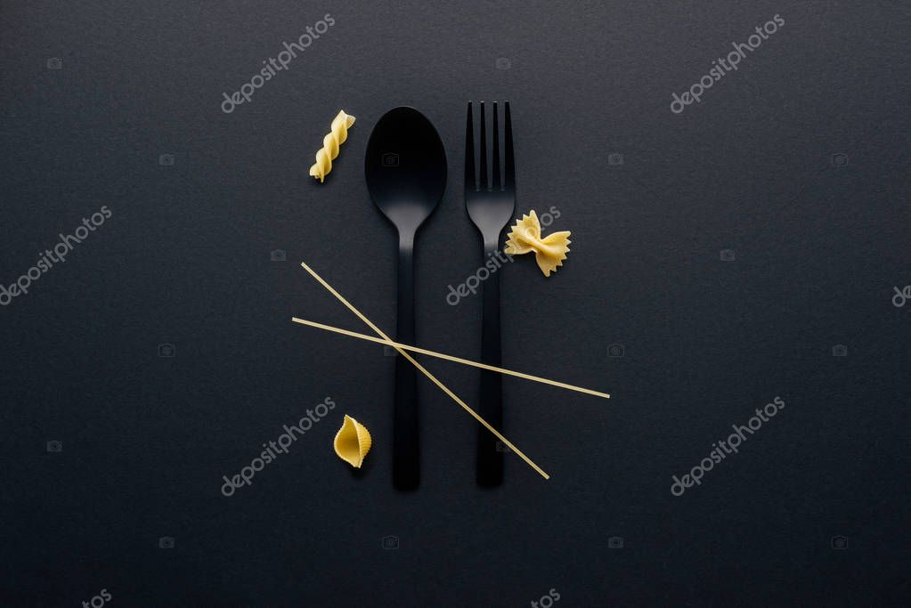 black plastic spoon, fork and four different kinds of pasta on black background