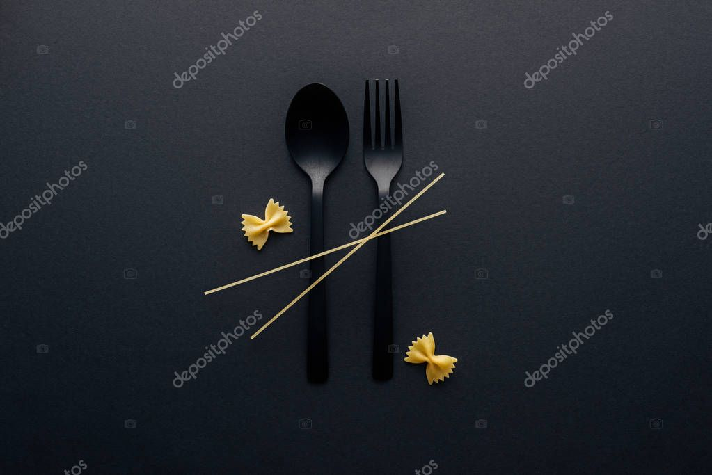 plastic spoon and fork with farfalle pasta and spaghetti on black background