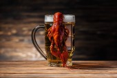 Fotografie glass with beer and red lobster on wooden surface