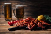 red lobsters, tomatoes, dill, lemon and glasses with beer on wooden surface
