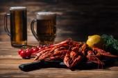Rote Hummer, Tomaten, Dill, Zitrone und Biergläser auf Holzoberfläche