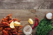 Fotografie top view of red lobsters, dill, lemon slices, pepper, glasses with beer and salt on wooden surface