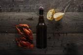 Draufsicht auf rote Hummer, Zitronenscheiben und Flasche mit Bier auf Holzoberfläche