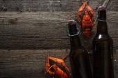Draufsicht auf rote Hummer und Bierflaschen auf Holzoberfläche