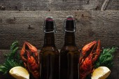 top view of red lobsters, dill, lemon slices and glass bottles with beer on wooden surface