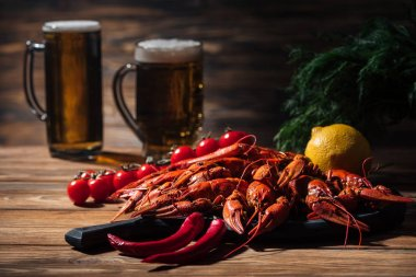 selective focus of red lobsters, tomatoes, dill, lemon and glasses with beer on wooden surface