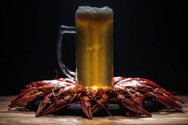 glass of beer on plate with red lobsters at wooden surface