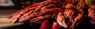 panoramic shot of red lobsters with peppers on wooden surface