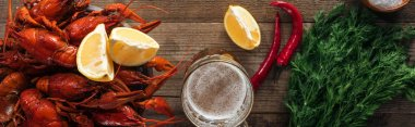 panoramic shot of red lobsters, dill, pepper, lemon slices and glass with beer on wooden surface