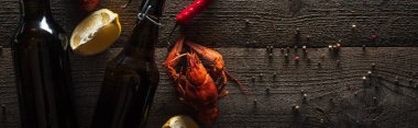 panoramic shot of red lobsters, lemon slices, peppers and bottles with beer on wooden surface