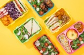 Top-Ansicht von Lunchboxen mit Lebensmitteln auf gelbem Hintergrund