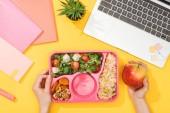abgeschnittene Ansicht einer Frau mit Lunchbox mit Lebensmitteln in der Nähe von Laptop und Büromaterial