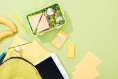 Draufsicht auf Lunchbox mit Sandwiches und Salat in der Nähe von Rucksack mit Schreibwaren