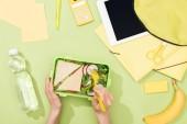 Fényképek levágott kilátás nő kezek műanyag edények több mint ebéd doboz élelmiszer közelében hátizsák, digitális tabletta, üveg víz és írószer