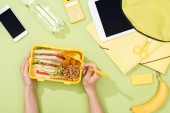 cropped view of woman hands with plastic utensils over lunch box with food near backpack, digital tablet, bottle of water and stationery