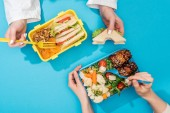 cropped view of two women holding forks over lunch boxes with food