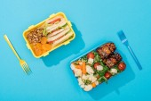 pohled na umělohmotné vidličky u krabic na oběd s jídlem na modrém pozadí