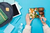 Fotografie Ausgeschnittene Ansicht einer Frau mit Lunchbox in der Nähe eines Rucksacks mit Ordnern, Schreibwaren, Wasserflasche und digitalem Tablet