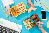 Photo cropped view of two women holding forks over lunch boxes with food near laptop