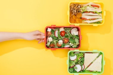 cropped view of woman choosing lunch boxes with food