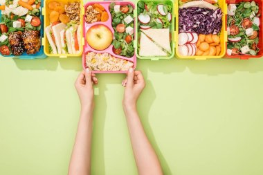 Cropped view of woman choosing lunch boxes with food on green background stock vector