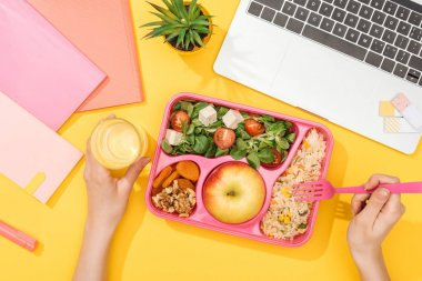 Cropped view of woman holding fork over lunch box with food near laptop and office supplies stock vector