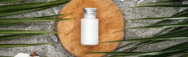 top view of coconut beauty product in bottle on wooden board near palm leaves, panoramic shot