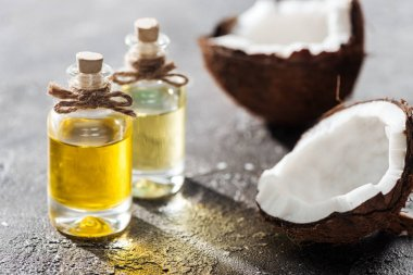 Selective focus of bottles with coconut oil near coconut halves on grey background stock vector